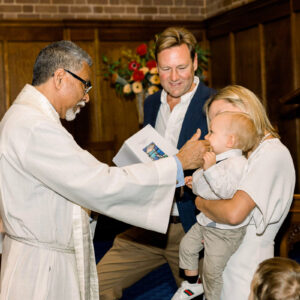 christening photography priest bless the baby boy by touching his nose